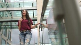 Το σύγχρονο κορίτσι έρχεται κάτω από τα σκαλοπάτια στο πάρκο πόλεων απόθεμα βίντεο
