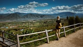 Το σύγχρονο κορίτσι με τις δερματοστιξίες φαίνεται άνωθεν μια όμορφη άποψη της πόλης Pai Φορά ένα σακίδιο πλάτης και ένα τζιν στοκ φωτογραφία με δικαίωμα ελεύθερης χρήσης