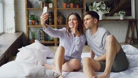 Το σύγχρονο παντρεμένο ζευγάρι παίρνει selfie στη gesturing τοποθέτηση κρεβατοκάμαρων και το φίλημα καθμένος στο κρεβάτι από κοιν απόθεμα βίντεο