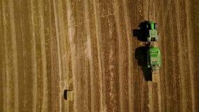 Το σύγχρονο τρακτέρ κάνει τις θυμωνιές χόρτου στον τομέα μετά από να συγκομίσει Εναέρια τοπ άποψη κινήσεων φιλμ μικρού μήκους