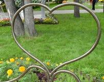 Το σύμβολο καρδιών σχεδίων μετάλλων, κοιτάζει μέσω της καρδιάς στη χλόη, πάρκο, Valentine& x27 ημέρα του s Στοκ Φωτογραφίες