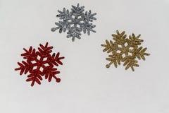 Το σύμβολο νιφάδων χιονιού με ακτινοβολεί στο κόκκινο, το ασήμι και το χρυσό για τη διακόσμηση και τη διακόσμηση Χριστουγέννων πο στοκ εικόνες με δικαίωμα ελεύθερης χρήσης