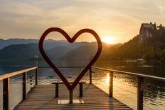 Το σύμβολο καρδιών στη γραφική ακτή της αιμορραγημένης λίμνης στο ηλιοβασίλεμα Στοκ εικόνα με δικαίωμα ελεύθερης χρήσης