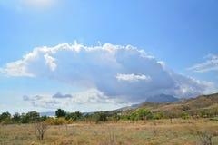Το σύννεφο εμφανίζεται από πίσω από τα βουνά στο Karadag Nati στοκ φωτογραφία