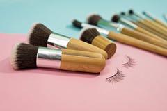 Το σύνολο βουρτσών makeup στο ροζ και το aqua χρωμάτισε το αποτελούμενο backgrou Στοκ Εικόνες