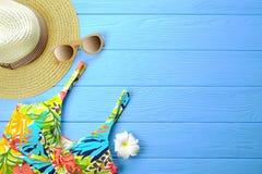 Το σύνολο ζωηρόχρωμων εξαρτημάτων γυναικών ` s στο μαγιό εποχής παραλιών, οι πτώσεις κτυπήματος, τα γυαλιά ηλίου και το καπέλο με Στοκ φωτογραφία με δικαίωμα ελεύθερης χρήσης
