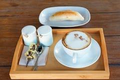 το σύνολο καφέ, cappuccino στο άσπρο φλυτζάνι καφέ με το ψωμί επιζητά επάνω Στοκ φωτογραφία με δικαίωμα ελεύθερης χρήσης