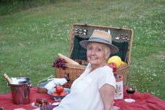 Το σύνολο της χαράς και ενός μοντέρνου καπέλου ήλιων, η όμορφη γυναίκα απολαμβάνει ένα πικ-νίκ στο πάρκο Στοκ Εικόνα