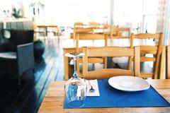 Το σύνολο του γυαλιού πιάτων, μαχαιροπήρουνων και κρασιού στον ξύλινο πίνακα στο εστιατόριο θολώνει στο υπόβαθρο Στοκ φωτογραφία με δικαίωμα ελεύθερης χρήσης