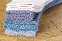 Το σύνολο χαριτωμένου μικρού διαφορετικού χρωματισμένου κασμιριού έπλεξε τις νεογέννητες κάλτσες μωρών σε ένα ξύλινο υπόβαθρο γρα Στοκ Εικόνα