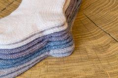 Το σύνολο χαριτωμένου μικρού διαφορετικού χρωματισμένου κασμιριού έπλεξε τις νεογέννητες κάλτσες μωρών σε ένα ξύλινο υπόβαθρο γρα Στοκ εικόνα με δικαίωμα ελεύθερης χρήσης