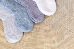 Το σύνολο χαριτωμένου μικρού διαφορετικού χρωματισμένου κασμιριού έπλεξε τις νεογέννητες κάλτσες μωρών σε ένα ξύλινο υπόβαθρο γρα Στοκ Φωτογραφία