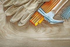 Το σύνολο ασφάλειας δέρματος φορά γάντια στα ξύλινα καρφιά σφυριών νυχιών μετρητών στο W Στοκ Εικόνα