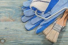 Το σύνολο κυλίνδρου χρωμάτων βουρτσίζει τα προστατευτικά γάντια στα ξύλινα μειονεκτήματα πινάκων Στοκ Εικόνες