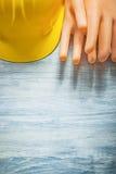 Το σύνολο μόνωσης φορά γάντια στο κράνος οικοδόμησης στο ξύλινο electri πινάκων Στοκ Εικόνα