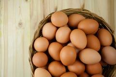 Το σύνολο των αυγών υπόβαλε ένα ψάθινο καλάθι στο ξύλινο υπόβαθρο Στοκ εικόνα με δικαίωμα ελεύθερης χρήσης