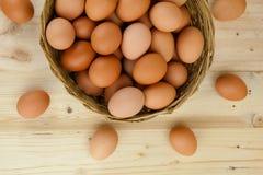 Το σύνολο των αυγών υπόβαλε ένα ψάθινο καλάθι στο ξύλινο υπόβαθρο Στοκ Φωτογραφία