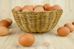 Το σύνολο των αυγών υπόβαλε ένα ψάθινο καλάθι στο ξύλινο υπόβαθρο Στοκ Εικόνες