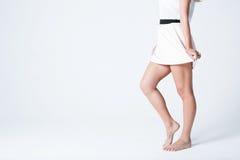 το σώμα ανασκόπησης μωρών δίνει λίγα πέρα από το λευκό μερών Όμορφα πόδια γυναικών σε μια φούστα Στοκ φωτογραφία με δικαίωμα ελεύθερης χρήσης