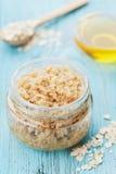 Το σώμα τρίβει oatmeal, της ζάχαρης, του μελιού και του ελαίου στο βάζο γυαλιού στον μπλε αγροτικό πίνακα, του σπιτικού καλλυντικ στοκ εικόνες με δικαίωμα ελεύθερης χρήσης