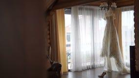 Το τέλειο άσπρο γαμήλιο φόρεμα κρεμά στην κρεμάστρα στο δωμάτιο νυφών Τα κομψά υψηλά τακούνια βρίσκονται κοντά στην εσθήτα απόθεμα βίντεο