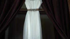 Το τέλειο γαμήλιο φόρεμα με σε μια κρεμάστρα στο δωμάτιο της νύφης με τις καφετιές κουρτίνες απόθεμα βίντεο