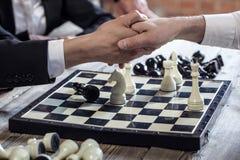 Το τίναγμα ανθρώπων παραδίδει τη σκακιέρα στοκ φωτογραφίες