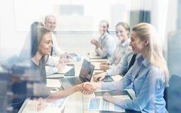 Το τίναγμα επιχειρηματιών χαμόγελου παραδίδει το γραφείο Στοκ φωτογραφίες με δικαίωμα ελεύθερης χρήσης