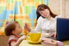 Το ταΐζοντας μωρό επιχειρηματιών και μιλά από κινητό Στοκ φωτογραφία με δικαίωμα ελεύθερης χρήσης
