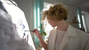 Το ταλαντούχο θηλυκό ζωγράφων με την έμπνευση σύρει με την εικόνα βουρτσών στον καμβά στο στούντιο τέχνης στο φυσικό φως ενάντια απόθεμα βίντεο