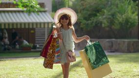 Το ταξίδι αγορών, ο μοντέρνος αγοραστής μικρών κοριτσιών στα γυαλιά ηλίου και το καπέλο φέρνουν τις αγορές στις τσάντες μετά από  απόθεμα βίντεο