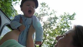 Το ταξίδι με το παιδί, μητέρα κρατά το γιο της στον αέρα στο υπόβαθρο των πράσινων δέντρων στο backlight απόθεμα βίντεο