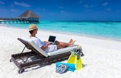 Το ταξιδιωτικό άτομο κάθεται σε μια τροπική παραλία με το lap-top και τις εργασίες του Στοκ φωτογραφίες με δικαίωμα ελεύθερης χρήσης