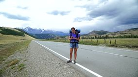Το ταξιδιωτικό κορίτσι με ένα σακίδιο πλάτης και τα γυαλιά ηλίου προσπαθεί να πιάσει το τηλεφωνικό σήμα σε έναν δρόμο βουνών Υπάρ φιλμ μικρού μήκους