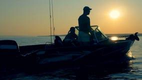 Το ταχύπλοο επιπλέει πέρα από μια λίμνη με δύο ψαράδες και εξοπλισμό αλιείας εν πλω απόθεμα βίντεο
