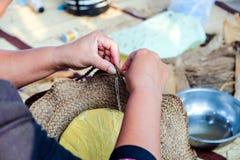 Το ταϊλανδικό θηλυκό artisans χρησιμοποιεί μια ύφανση βελόνων ράβει το καπέλο που υφαμένος προέρχεται από τις εγκαταστάσεις Στοκ Εικόνες
