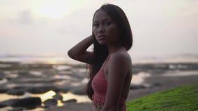 Το ταϊλανδικό νέο πρότυπο στο ροζ έπλεξε τη τοπ τοποθέτηση ενάντια στο σκηνικό του ηλιοβασιλέματος απόθεμα βίντεο