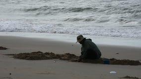 Το ταϊλανδικό σκάψιμο κουταλών χρήσης ανθρώπων ηλικιωμένων γυναικών βρίσκει το κοχύλι και τα οστρακόδερμα στην παραλία απόθεμα βίντεο