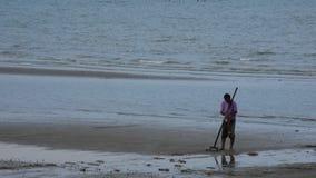 Το ταϊλανδικό σκάψιμο τσουγκρανών χρήσης ανθρώπων ατόμων βρίσκει τα οστρακόδερμα στην παραλία στο Σουράτ Thani, Ταϊλάνδη φιλμ μικρού μήκους