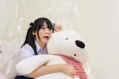 Το ταϊλανδικό κορίτσι γυμνασίου στα γυαλιά παρουσιάζει ότι η συγκλονίζοντας έκφραση αγκαλιάζοντας teddy αντέχει Στοκ εικόνες με δικαίωμα ελεύθερης χρήσης