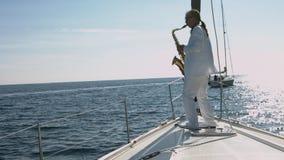 Το ταλαντούχο saxophonist εκτελεί την τζαζ στο άσπρο γιοτ πολυτέλειας απόθεμα βίντεο