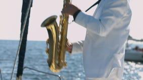 Το ταλαντούχο saxophonist εκτελεί την τζαζ στο saxophone στο γιοτ απόθεμα βίντεο
