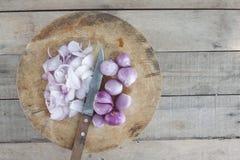 Το τεμαχισμένα ξεφλουδισμένα κρεμμύδι και το μαχαίρι στον τέμνοντα πίνακα μαγειρεύουν τα συστατικά στοκ εικόνες