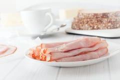 Το τεμαχισμένο ζαμπόν κύλησε επάνω στο άσπρο πιάτο στοκ εικόνα με δικαίωμα ελεύθερης χρήσης
