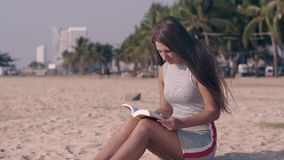 Το τεράστιο κορίτσι στο ελαφρύ φόρεμα διαβάζει τη συνεδρίαση βιβλίων στην άμμο απόθεμα βίντεο