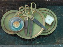 Το τεράστιο ψαλίδι μετάλλων 2 κομμάτια βρίσκεται δίπλα-δίπλα στο χαλκό γύρω από τα πιάτα, στο αριστερό είναι παλαιά στρογγυλά ρολ Στοκ Φωτογραφία