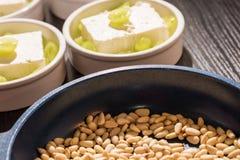 Το τηγάνι με τα καρύδια πεύκων για ένα επιδόρπιο Στοκ Φωτογραφία