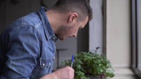 Το τηγάνι της ανάγνωσης νεαρών άνδρων κρατά κοντά στο παράθυρο φιλμ μικρού μήκους