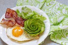 Το τηγανισμένα αυγό, το μπέϊκον και το αβοκάντο αυξήθηκαν για το πρόγευμα Στοκ φωτογραφία με δικαίωμα ελεύθερης χρήσης