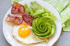 Το τηγανισμένα αυγό, το μπέϊκον και το αβοκάντο αυξήθηκαν για το πρόγευμα Στοκ Εικόνες